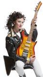 Flickasammanträde på stolen med den electro gitarren Arkivfoton