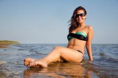 Flickasammanträde på stranden Royaltyfria Bilder