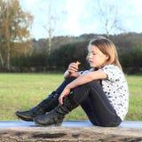 Flickasammanträde på trä Royaltyfria Bilder