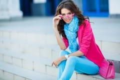 Flickasammanträde på trappa i färgrik kläder fotografering för bildbyråer