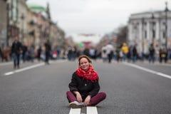 Flickasammanträde på vägen i mitt av gatan royaltyfri fotografi