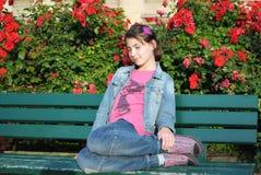 Flickasammanträdet på bänken arkivfoto