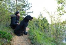 Flickasammanträde med hunden på äng Royaltyfri Bild