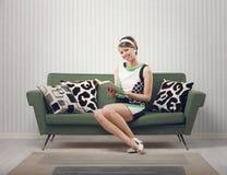 Flickasammanträde på soffan Arkivbild
