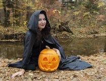 Flickasammanträde vid floden med pumpa Royaltyfri Foto
