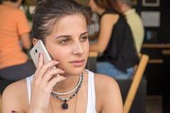 Flickasamtal till den smarta telefonen i en coffee shop Milt leende på framsidan arkivbild
