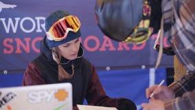 Flickashowmannen skidar in likformign gör häftet in att campa på skidar semesterorten folk stock video