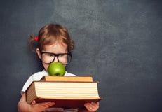 Flickaskolflicka med böcker och äpplet i en skolförvaltning Arkivfoto