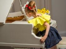 Flickaskolflicka nära pianot som ligger på en bukett av blomman Royaltyfri Foto