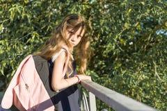 Flickaskolflickablondin med ryggs?cken i skolalikformig n?ra staketet i skolg?rd royaltyfri fotografi