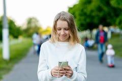 Flickaskolflickablondin Sommar i natur I händer som rymmer en smartphone som lyssnar till musik på telefonen Meddelar in Arkivbilder