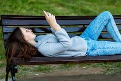 Flickaskolflickabrunett i sommar i en parkera som ligger på en bänk I händerna av att rymma läser skriver en smartphone och till royaltyfri fotografi