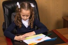 Flickaskolflickan drar en kulör blyertspenna royaltyfria foton