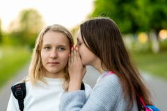 Flickaskolflickatonåringar, i sommar parkerar in och att tala på örat Begreppet av hemligheten, fantasi, tanke sinnesrörelser royaltyfria bilder