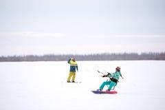 Flickasnowboarderen rider Snowkiting i fältet Arkivfoto