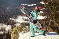 Flickasnowboarderen tycker om skidasemesterorten Royaltyfri Fotografi