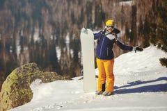 Flickasnowboarderen tycker om skidasemesterorten Arkivfoto
