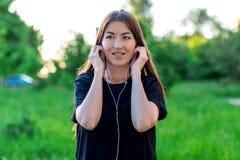 Flickasommar i en parkera i natur Hänglsen ler lyckligt på tänder Hon sätter på hörlurar och lyssnar till musik emotionellt Royaltyfri Foto