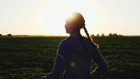Flickaspring längs fältet på solnedgången lager videofilmer