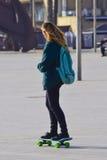 Flickaspring på en skateboard Arkivfoton