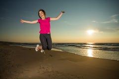 Flickaspring på stranden Arkivbilder