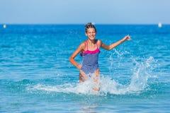 Flickaspring till och med vattnet Arkivfoto