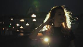 Flickastående i kontur med hår som vinkar i brisen på nattstadsbakgrund Ljust hår i stadsljusen brand stock video