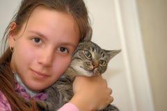 Flickastående som kramar en katt royaltyfri foto