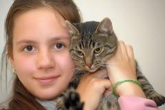 Flickastående som kramar en katt royaltyfria foton