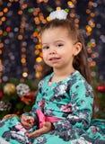 Flickaståenden i julgarnering med gåvan, mörk bakgrund med belysning och boke tänder, begreppet för vinterferie Royaltyfri Foto
