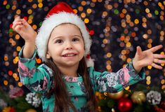Flickaståenden i julgarnering med gåvan, mörk bakgrund med belysning och boke tänder, begreppet för vinterferie Arkivbild