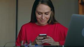 Flickastudent med den röda tröjabrukssmartphonen i arbetsplats hemma arkivfilmer