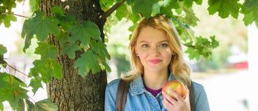 Flickastudent med ryggsäckhålläpplet medan ställning nära träd Studentlivbegrepp Tagandeminut som ska kopplas av Avbrott för royaltyfria foton