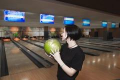 Flickastudent som spelar bowling En blick för kastet i bowlingleken mot bakgrunden av spåren Arkivfoto