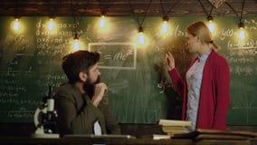 Flickastudenten passerar examen Lärare och deltagare tillbaka skola till Den uppsökte läraren med exponeringsglas undervisar stud lager videofilmer