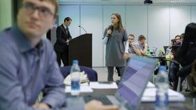 Flickastudenten talar på ett seminarium på universitetet genom att använda en mikrofon och projektorn Modern klassrumanvisning arkivfilmer