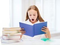 Flickastudera och läsebok på skolan Fotografering för Bildbyråer