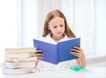 Flickastudera och läsebok på skolan Arkivfoton