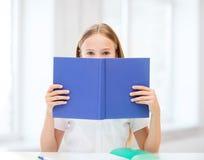 Flickastudera och läsebok på skolan Royaltyfri Bild