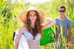 Flickasurfare med strandhatten som går med surfingbrädan Arkivfoto