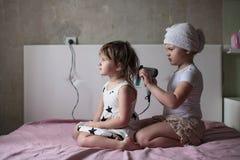 Flickasyskonet torkade sig & x27; s-hår, systrar som att bry sig för varje Arkivfoton