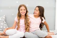 Flickasystrar spenderar angenäm tid för att meddela i sovrum Äldre systrar eller mer ung viktig faktor i syskon som mer har arkivbild