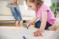 Flickateckning i vardagsrummet med modersammanträde bakom Fotografering för Bildbyråer