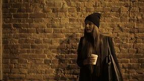 Flickatonåring i gatan på natten som dricker kaffe och att vänta