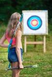 Flickatonåring med pilbågen och pilar framme av målet Royaltyfria Foton