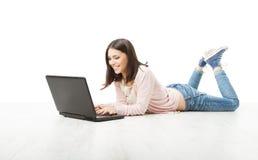 Flickatonåring som använder den trådlösa bärbara datorn. Kvinnamaskinskrivning i datoren ly Fotografering för Bildbyråer