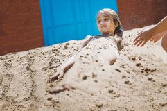 Flickatonåringar som gräver sig in i sanden på stranden royaltyfri foto