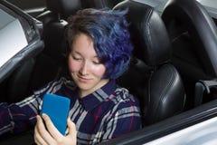 Flickatonåringchaufför som ler, medan se text på cellen Royaltyfri Bild