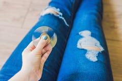 Flickatonåringen i holey jeans rymmer i händer och spelar med spinn royaltyfria foton