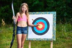 Flickatonåringen med pilbågen och pilen nära uppsätta som mål Arkivfoto